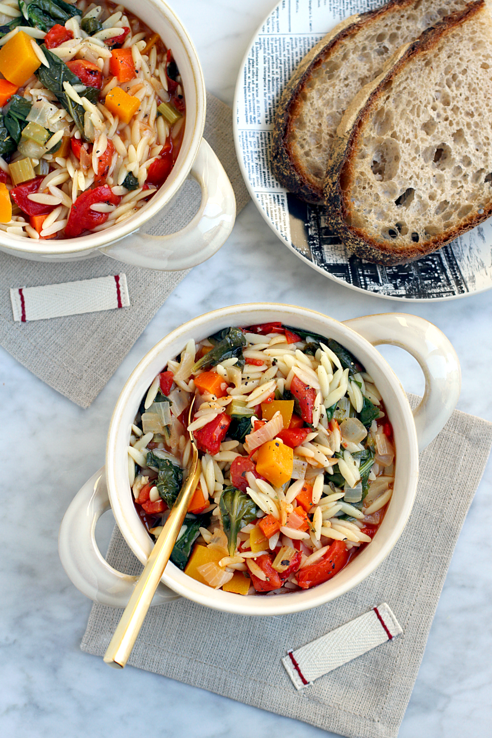 Image of vegetable and orzo soup from the top.
