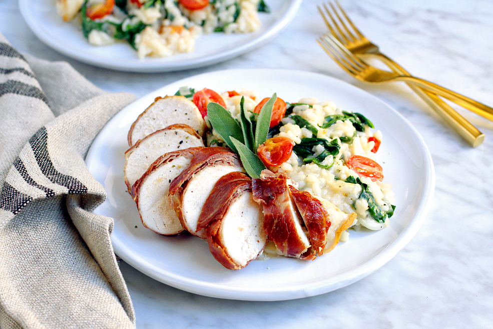 Close-up image of prosciutto-wrapped chicken with tomato and spinach risotto.