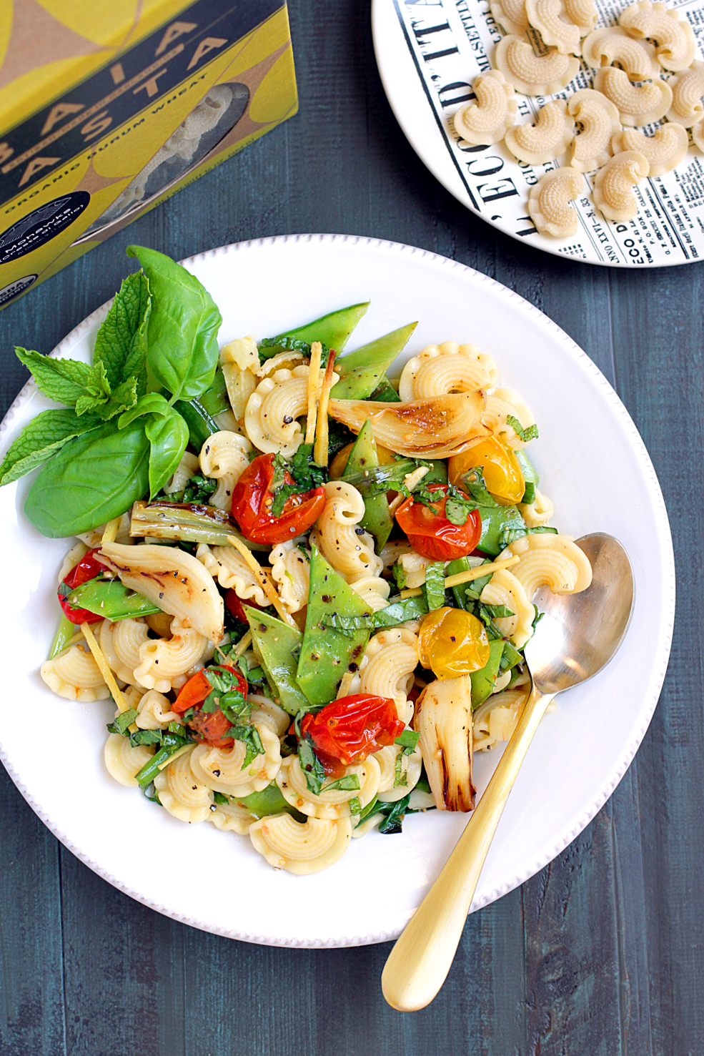 Image of pasta salad with roasted tomatoes, snow peas and spring onions.