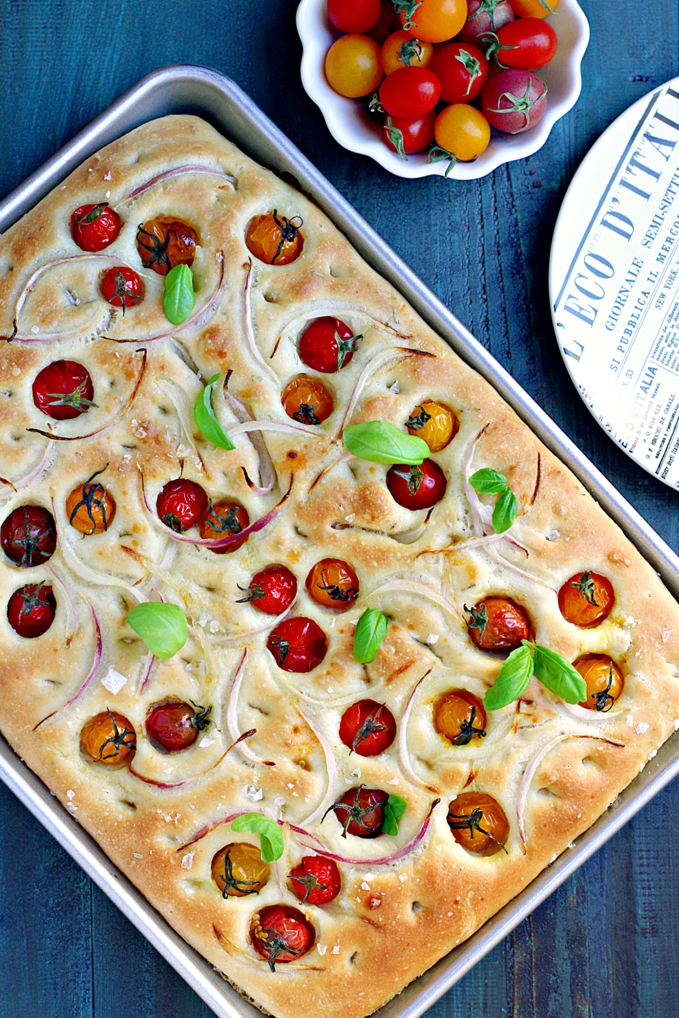 Image of focaccia with cherry tomatoes and red onions.