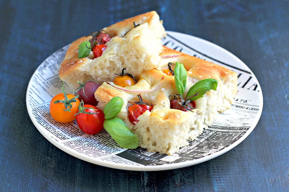 Image of a piece of focaccia with cherry tomatoes and red onions.