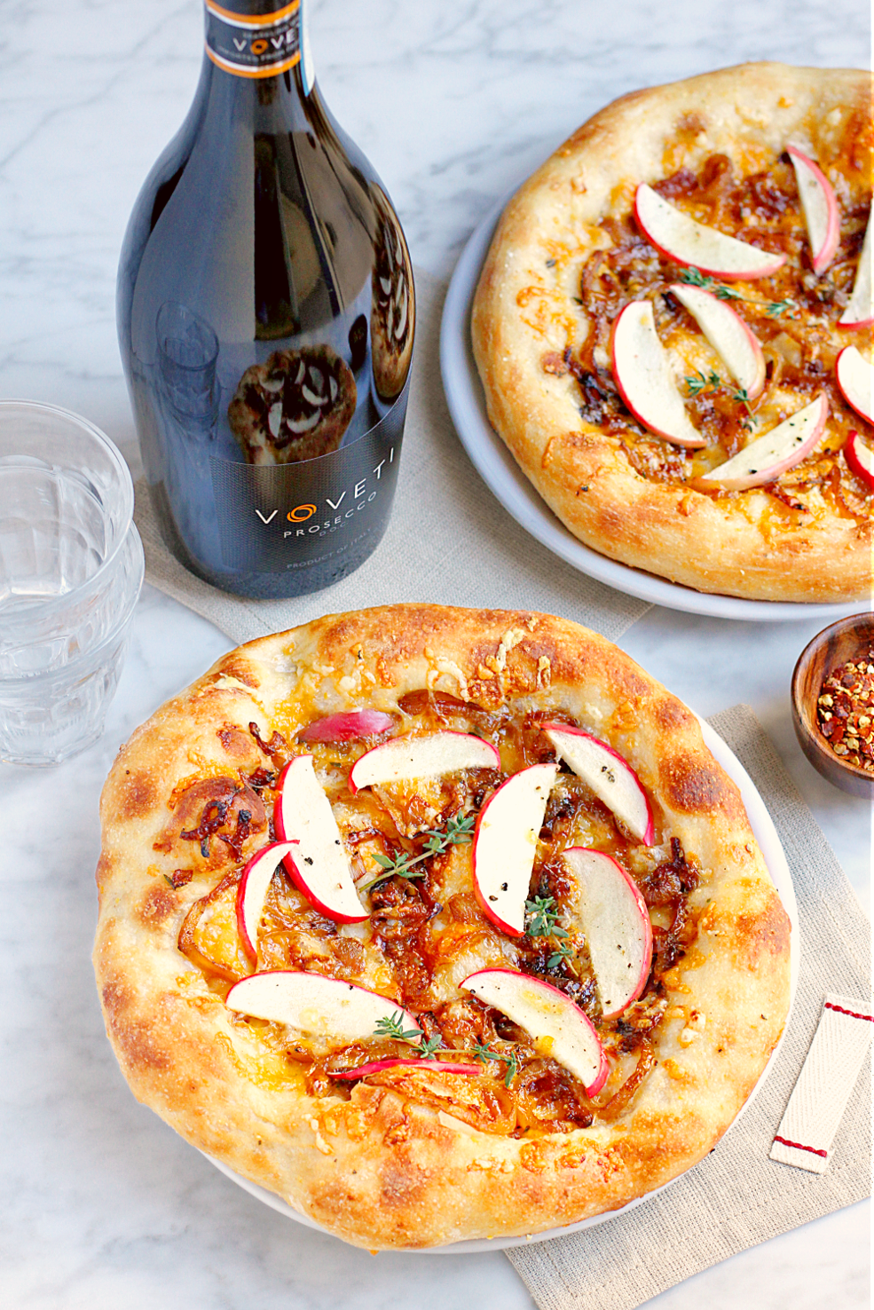 Image of apple and caramelized onion pizza and VOVETI Prosecco.