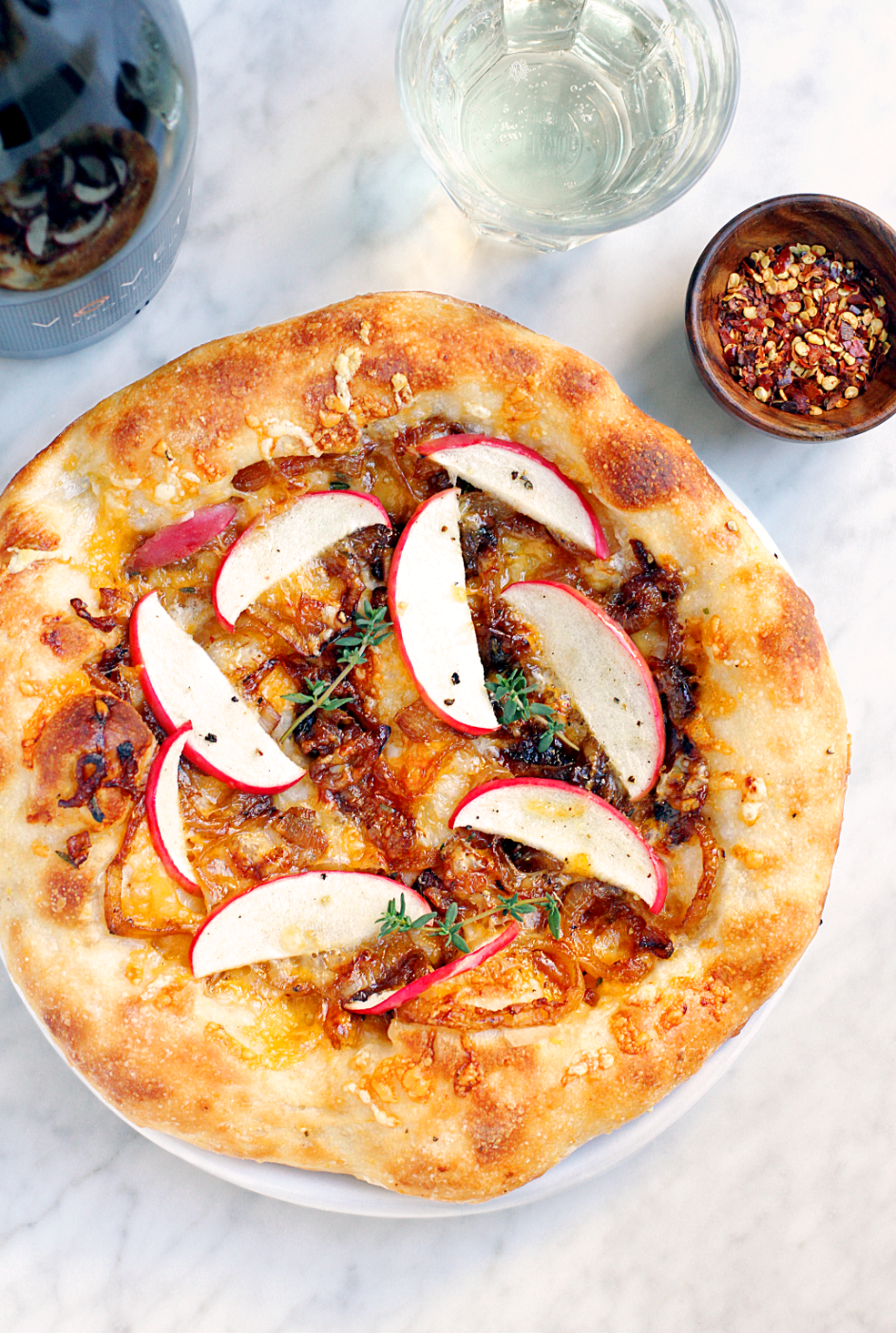 Close-up image of apple and caramelized onion pizza and VOVETI Prosecco.