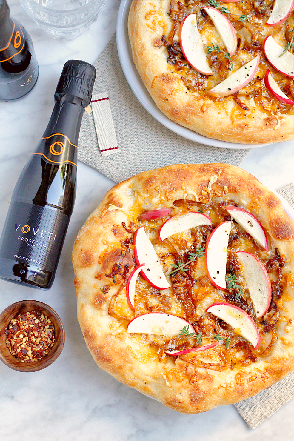 Image of apple and caramelized onion pizza and VOVETI Prosecco from the top.